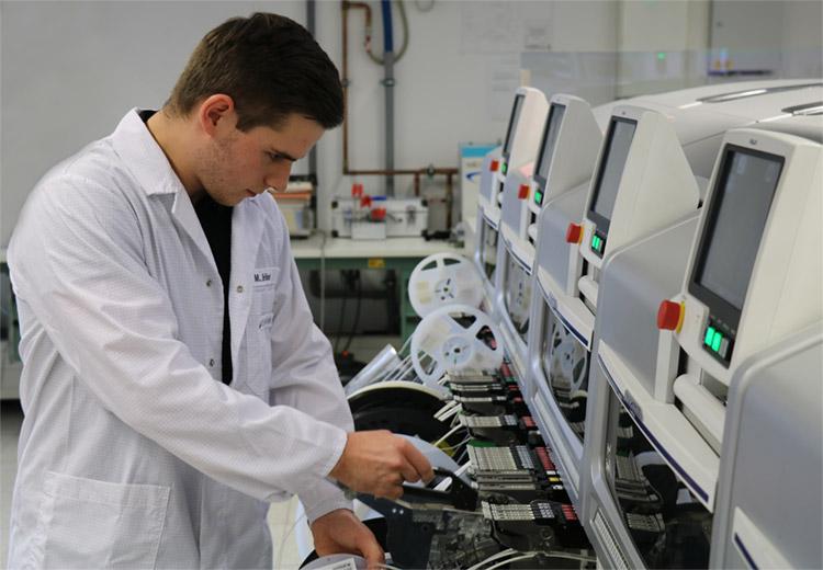 Marius Hänel rüstet den SMD-Bestückungsautomaten für den nächsten Auftrag um. Die Bauteilversorgungsstation (Feeder) bestückt er dazu mit Rollen für die auf Bändern fixierten SMD-Bauelemente.