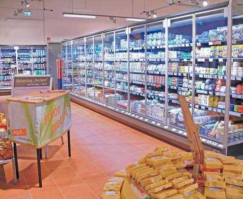 Meubles frigorifiques vitrés pour produits laitiers (rayons Mopro = produits laitiers) dans un supermarché d'alimentation de tegut…