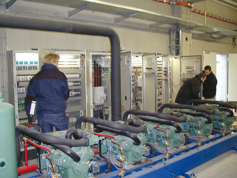 At the commissioning: refrigeration rack and switch cabinets in a large cold storage warehouse